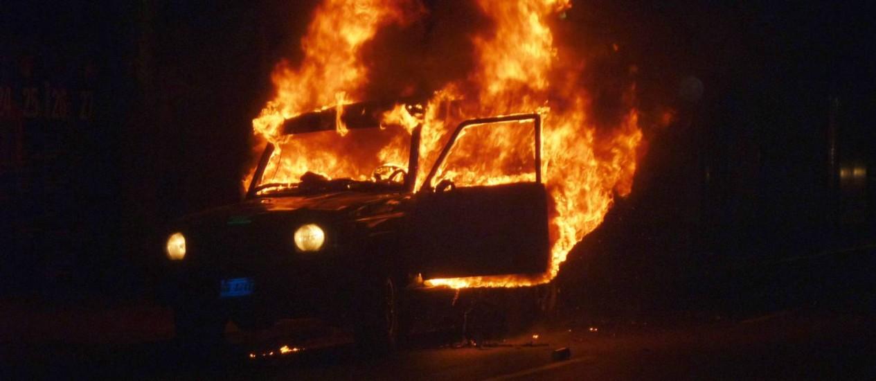 Um carro da Guarda Nacional é incendiado em Caracas. A polícia responsabilizou manifestantes Foto: GERALDO CASO / AFP