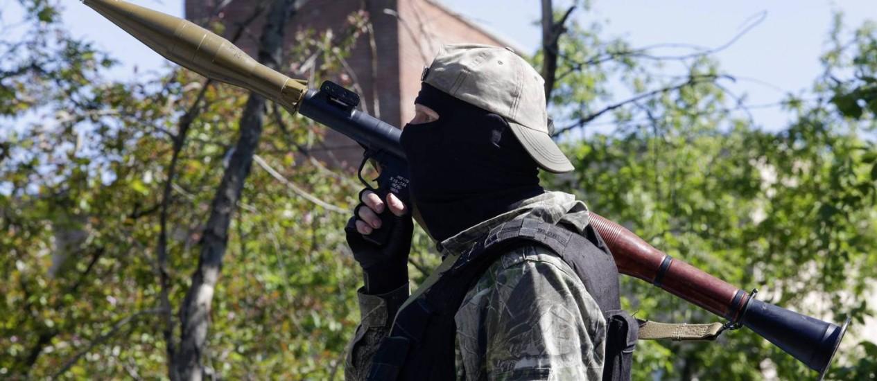 Separatista pró-Rússia anda armado pelas ruas de Donetsk, na Ucrânia Foto: Konstantin Chernichkin / REUTERS