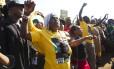 Partidários do Congresso Nacional Africano (CNA) cumprimentam o presidente da África do Sul, Jacob Zuma (não retratado), depois de ele ter votado em um posto de votação no distrito de Nkandla