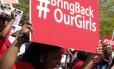 Manifestante segura cartaz pedindo ajuda para encontrar jovens sequestradas do lado de fora da embaixada da Nigéria, em Washington