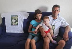Jaílton com as filhas Yasmin e Ester, ao lado da camisa com a foto de Fabiane Foto: Marcos Alves/ O Globo