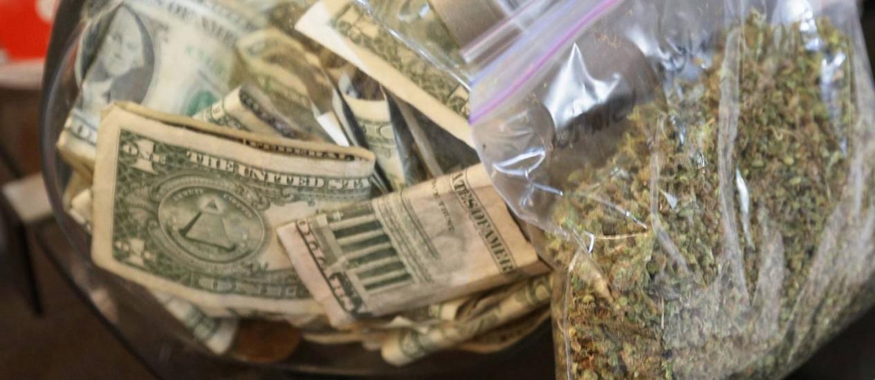 Um saco de maconha sendo preparado para a venda perto de um pote de dinheiro no estado do Colorado, onde a droga é legalizada Foto: RICK WILKING / REUTERS