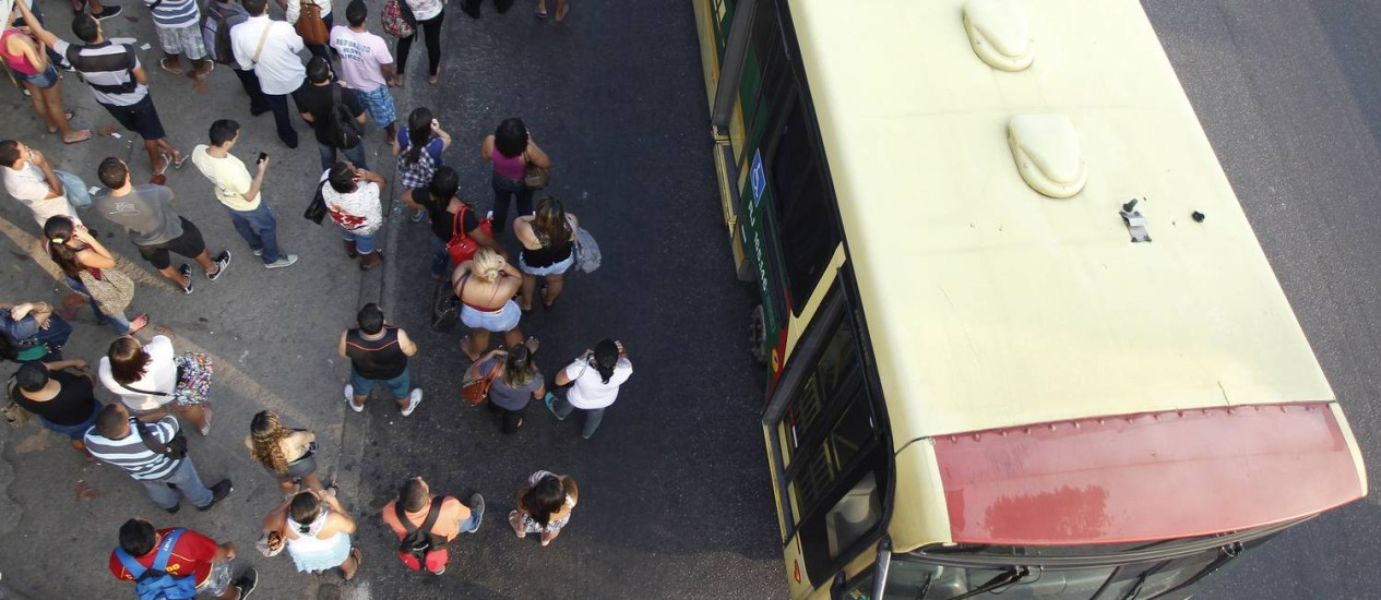 Passageiros num ponto de ônibus lotado da Avenida Brasil nesta quinta-feira: prefeitura prepara plano de contingência na volta para casa Foto: Agência O Globo / Antonio Scorza