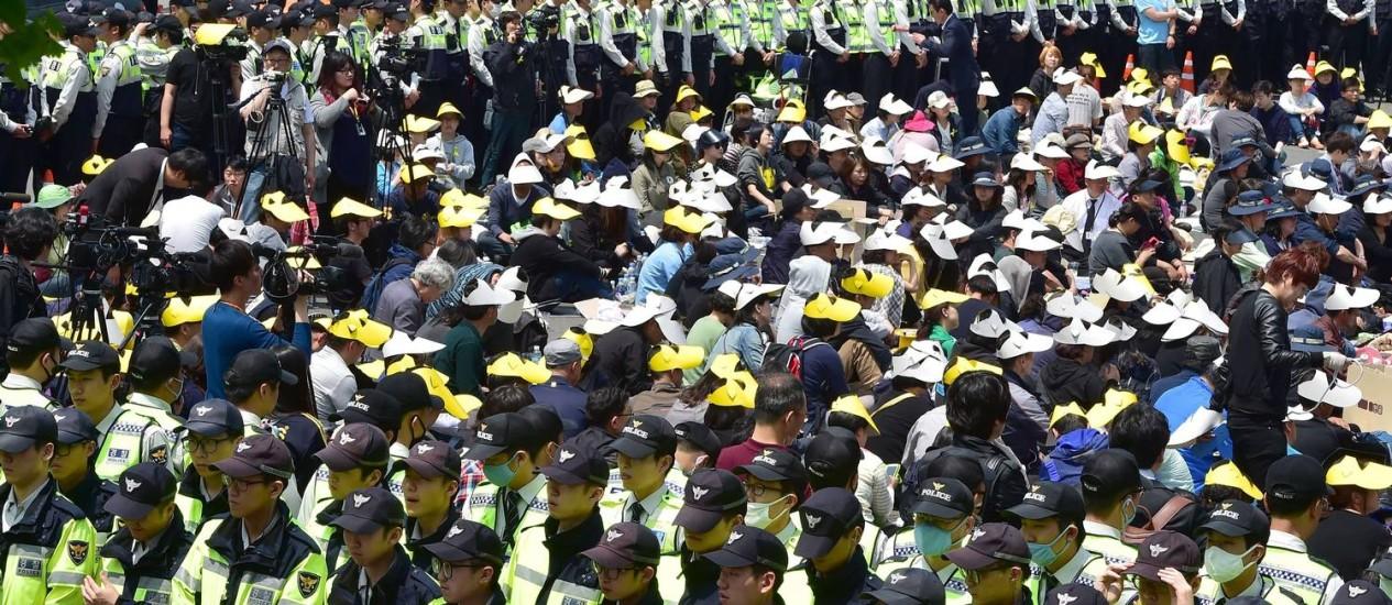 Policiais cercam parentes das vítimas do naufrágio da balsa Sewol em rua perto da sede do governo sul-coreano Foto: JUNG YEON-JE / AFP