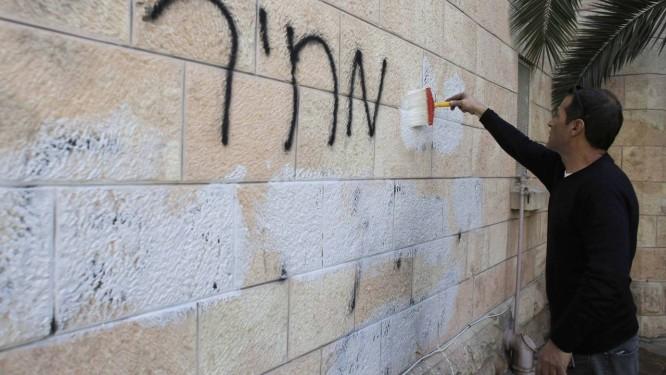 Funcionário da prefeitura limpa pichação no muro de igreja cristã: ultranacionalistas exigem que governo 'pague' por medidas que consideram pró-palestinos Foto: AMMAR AWAD/REUTERS