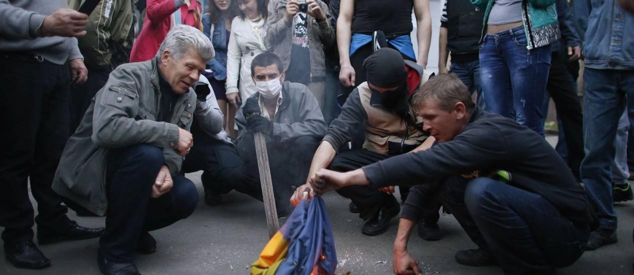 Separatistas pró-Rússia queimam bandeira ucraniana em protesto na cidade de Donetsk Foto: MARKO DJURICA / REUTERS