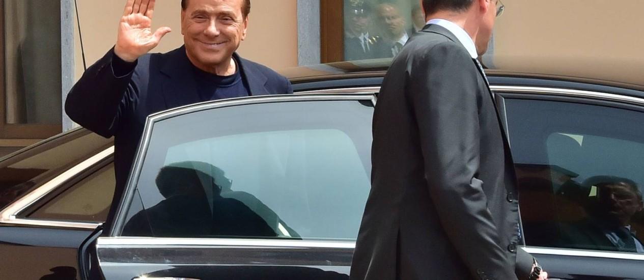 Ex-premier italiano Silvio Berlusconi acena após cumprir primeiro dia de trabalho comunitário, por decisão judicial: político é associado a um dos símbolos de corrupção no país Foto: GIUSEPPE CACACE / AFP