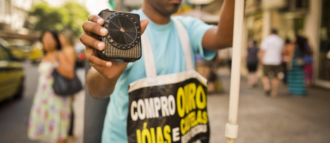 Funcionário da Ouro Mil com um dos quatro radinhos usados para propaganda: texto gravado por radialista Foto: Fábio Seixo / Agência O Globo