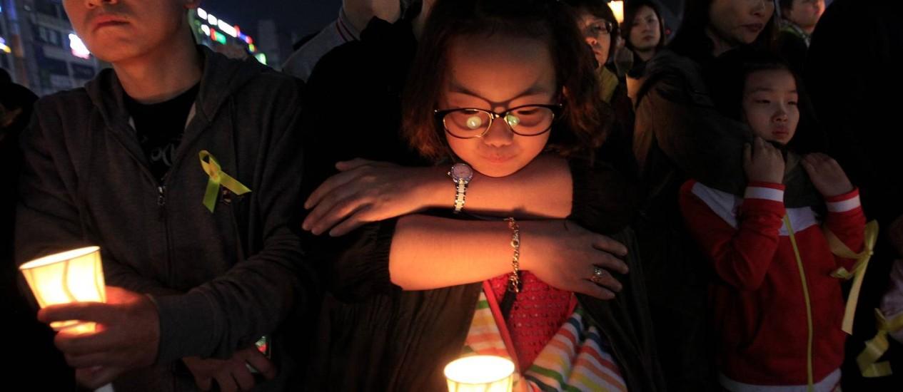 Menina segura vela durante ato para homenagear vítimas do naufrágio Foto: Ahn Young-joon / AP