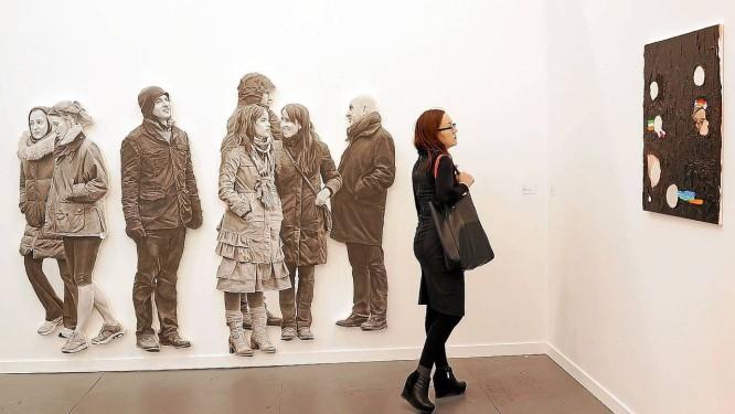Mulher observa obras na feira de arte Frieze Foto: SPENCER PLATT / AFP