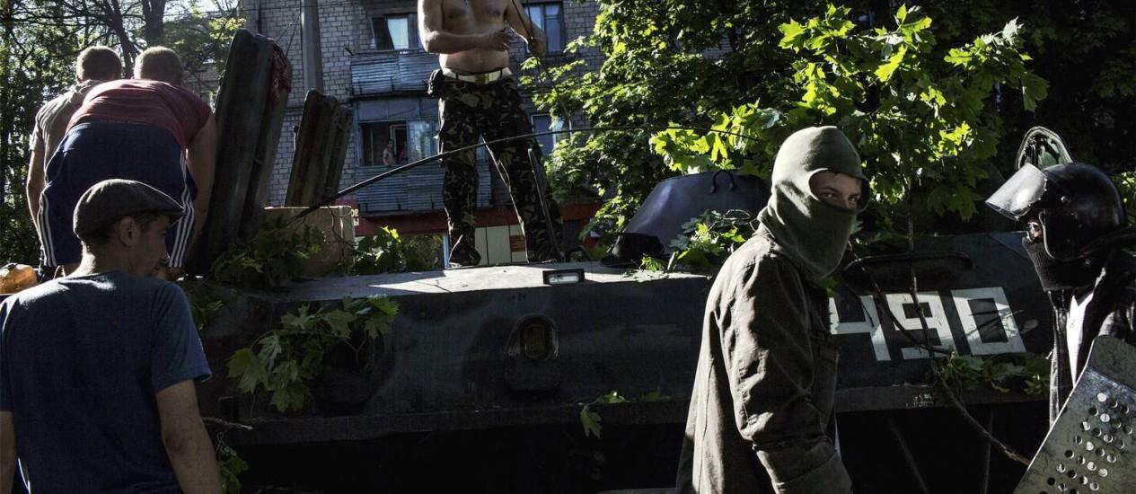 Ativista pró-Rússia sobe em um tanque que pertencia ao exército da Ucrânia no sudeste do país Foto: FABIO BUCCIARELLI / AFP