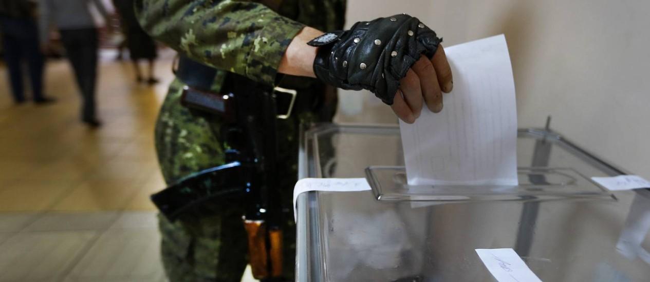 Soldado armado vota numa seção em Slaviansk, no Leste da Ucrânia Foto: YANNIS BEHRAKIS / REUTERS