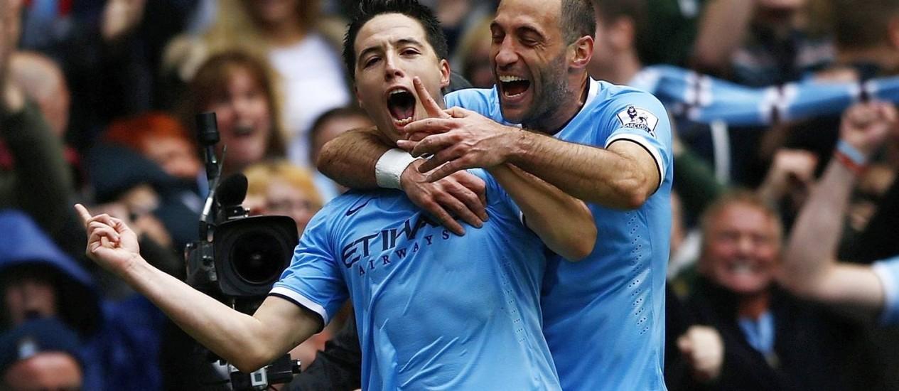 Samir Nasri, abraçado por Pablo Zabaleta, festeja o gol que marcou sobre o West Ham, no Campeonato Inglês: Manchester City campeão Foto: DARREN STAPLES / REUTERS