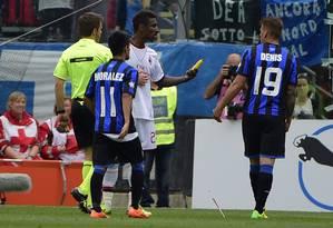 Constant, do Milan, pega a banana arremessada contra ele para entregar ao árbitro do jogo contra o Atalanta: mais um caso de racismo no futebol europeu, agora na Itália Foto: Oliver Morin / AFP