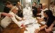 Membros da comissão eleitoral esvaziam uma urna após a votação em Donetsk