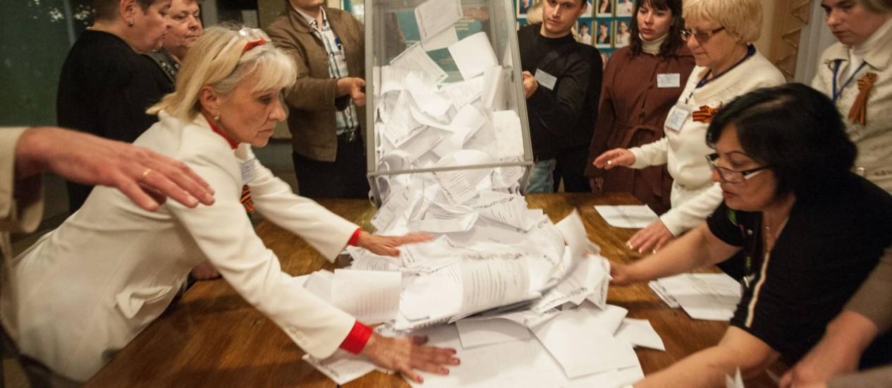 Membros da comissão eleitoral esvaziam uma urna após a votação em Donetsk Foto: Evgeniy Maloletka / AP