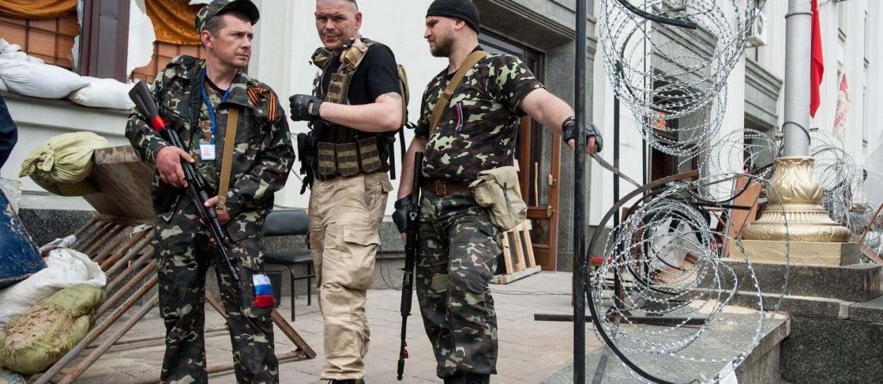 Homens armados pró-russos em frente à prefeitura na cidade de Luhansk Foto: Evgeniy Maloletka / AP
