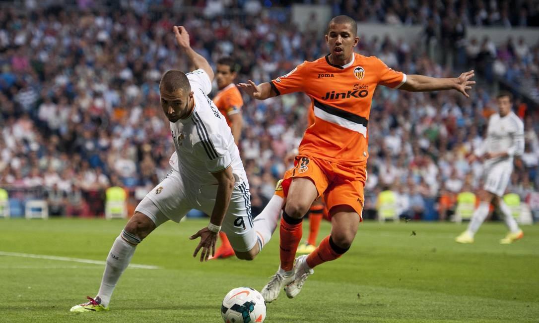 Feghouli, com a camisa laranja do Valencia, disputa a jogada com Karim Benzema do Real Madrid. Jogador argelino é presença certa no Brasil para a disputa da Copa Foto: / Dani Pozo / AFP