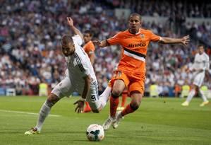 Feghouli, com a camisa laranja do Valencia, disputa a jogada com Karim Benzema do Real Madrid. Jogador argelino é presença certa no Brasil para a disputa da Copa Foto: Dani Pozo / AFP