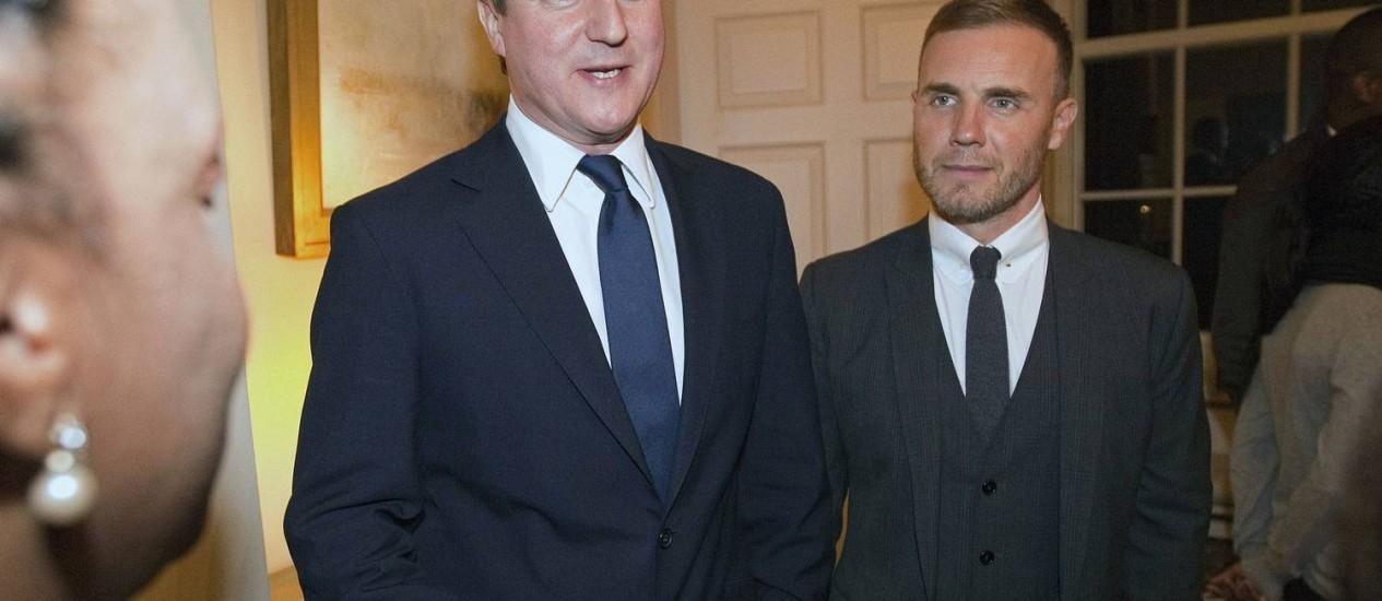 David Cameron (esquerda) e Gary Barlow: primeiro-ministro defende que astro pop não seja destituído de medalha concedida pela monarquia Foto: RICHARD POHLE / AFP
