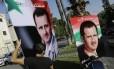 Homens penduram cartazes com a imagem do presidente Bashar al-Assad numa rua de Damasco. Crimes de guerra de forças governamentais seriam 'muito superiores' aos dos rebeldes, diz chefe do departamento de Direitos Humanos da ONU
