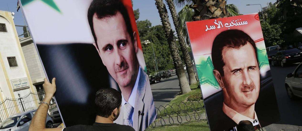 Homens penduram cartazes com a imagem do presidente Bashar al-Assad numa rua de Damasco. Crimes de guerra de forças governamentais seriam 'muito superiores' aos dos rebeldes, diz chefe do departamento de Direitos Humanos da ONU Foto: JOSEPH EID / AFP