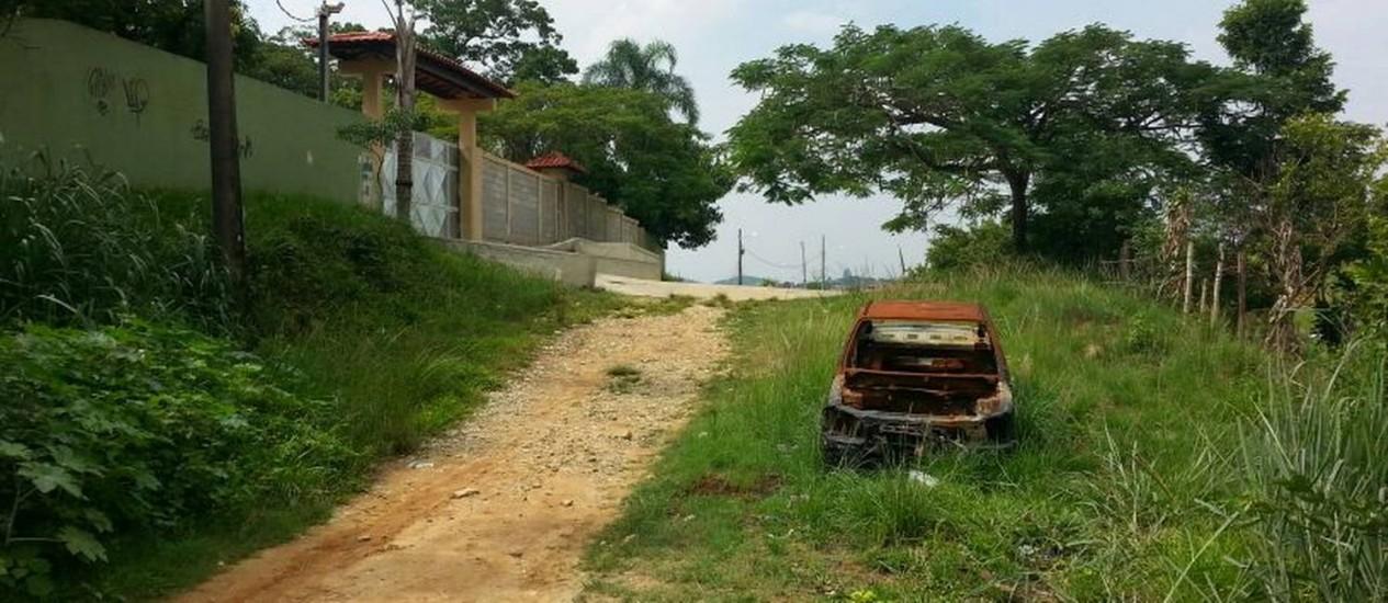 Carcaça de carro abandonada na Alameda Boa Esperança: rua cheia de mato e sem asfalto Foto: Leitora Maria Salomé Estrela Soares / Eu-Repórter