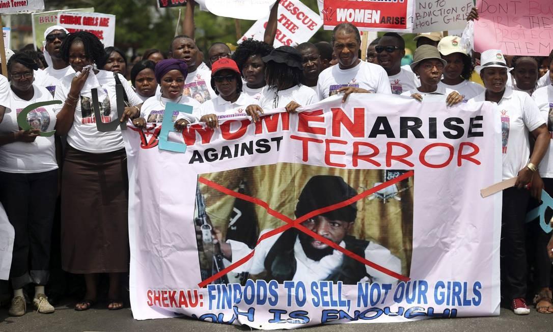 Na cidade nigeriana de Lagos, dezenas de pessoas carregam faixa com imagem do líder Abubakar Shekau, do grupo Boko Haram, durante protesto pela libertação das meninas sequestradas na remota aldeia de Chibok Foto: AKINTUNDE AKINLEYE / REUTERS