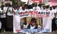 Na cidade nigeriana de Lagos, dezenas de pessoas carregam faixa com imagem do líder Abubakar Shekau, do grupo Boko Haram, durante protesto pela libertação das meninas sequestradas na remota aldeia de Chibok