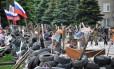Bandeiras russas tremulam em uma barricada diante da sede do governo regional ocupada por separatistas em Donetsk