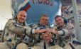 Cosmonautas russos dão as mãos a astronauta americano, à direita, em centro de treinamento