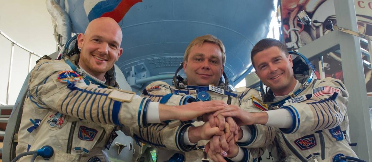 Cosmonautas russos dão as mãos a astronauta americano, à direita, em centro de treinamento Foto: AFP-7-5-2014
