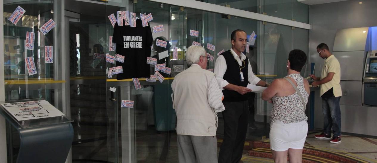 Funcionário de banco orienta clientes em agência em Copacabana: na parede, colete indica que vigilantes estão em greve Foto: Fábio Guimarães / Agência O Globo