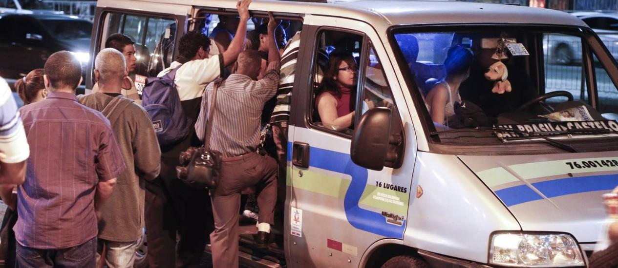 Sem ônibus, passageiros disputam lugar em van na Central: secretário diz que apenas 18% da frota de ônibus circulava às 18h desta terça-feira Foto: Guito Moreto / Agência O Globo