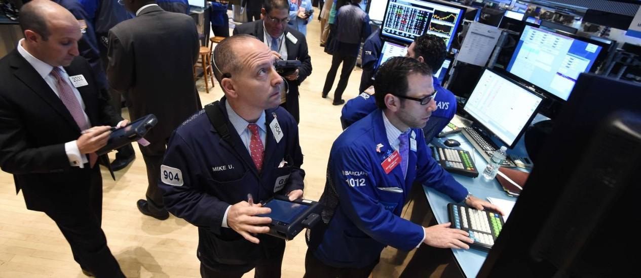 Ganho. Pregão de Nova York: bolsa americana subiu 10,76% em 12 meses. Bovespa caiu 0,99% Foto: STAN HONDA / AFP