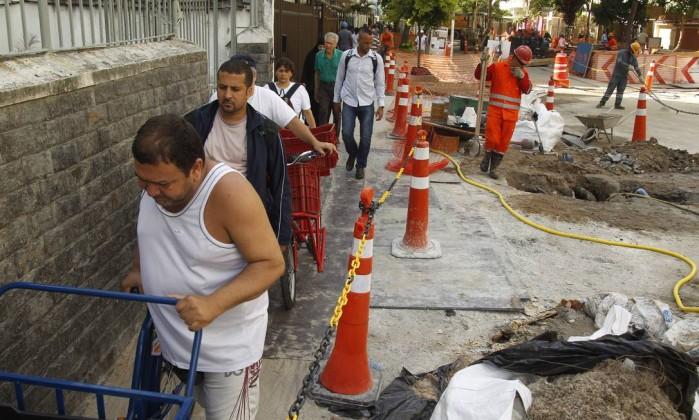 Pedestres passam com dificuldades em calçada perto de crateras em Ipanema Foto: Gabriel de Paiva / Agência O Globo