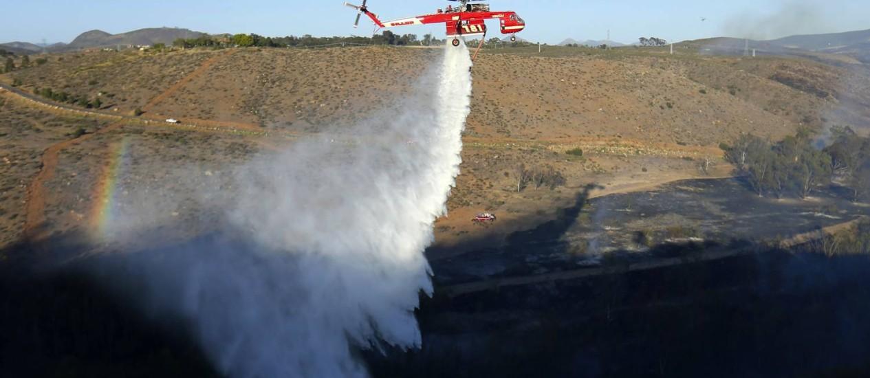 Helicóptero lança jatos de água próximo às casas ao norte de San Diego Foto: Mike Blake / Reuters