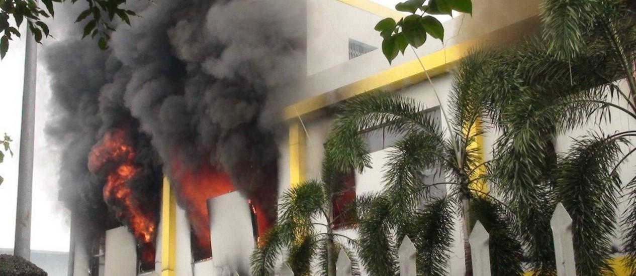 Fumaça e chamas saem da janela de uma fábrica incendiada por manifestantes anti-China em Binh Duong Foto: VNExpress / AFP