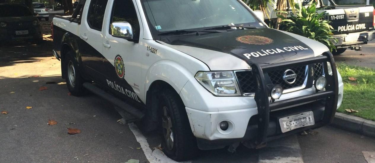 Carro da polícia com pneu arriado em frente à Delegacia de Homicídios - Foto: Leitor Felipe Borges / Eu-Repórter