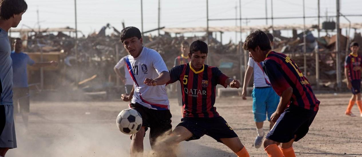 Jovens se divertem em um campo de Cidade de Sadr, em Bagdá Foto: BECHERER / The Washington Post