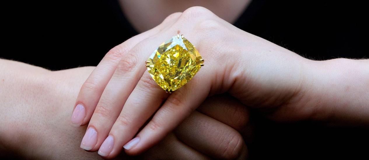 """Funcionária da Sotheby's exibe o """"Graff Vivid Yellow"""", diamante raro de 100,09 quilates Foto: ANDREW COWIE/AFP/11-4-2014"""