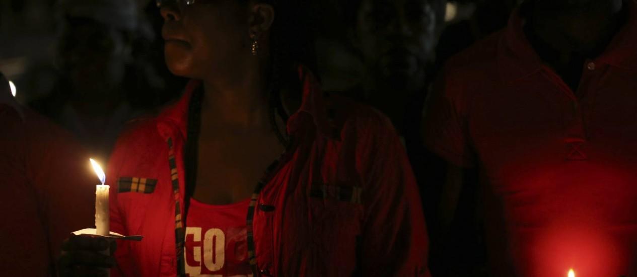 Mulher segura velas em reza por retorno seguro de meninas sequestradas Foto: AKINTUNDE AKINLEYE/REUTERS