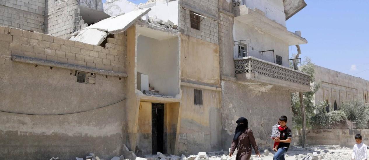 Civis caminham em uma rua cheia de escombros de edifícios danificados por ataques aéreos em Aleppo Foto: HOSAM KATAN / Reuters