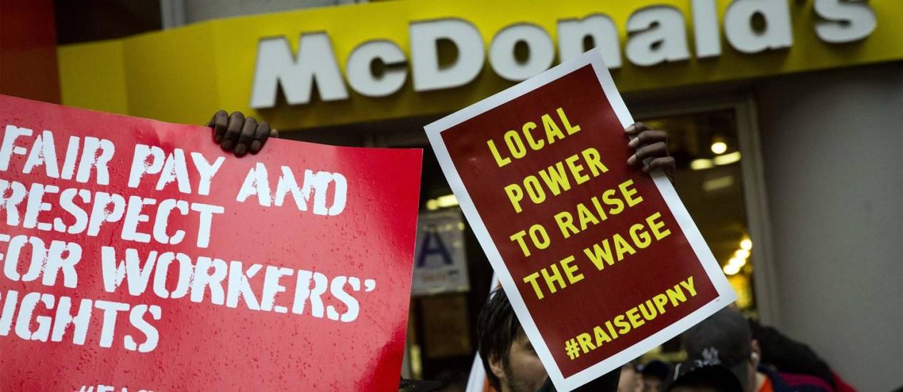 Manifestantes em restaurante do McDonald's em Nova York: empresas argumentam que aumento do salário vai reduzir postos de trabalho nos EUA Foto: Brendan McDermid/Reuters