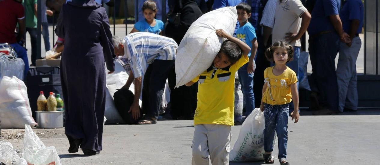 Crianças sírias carregam seus pertences ao atravessar a fronteira com a Turquia. Região que divide os dois países é palco de constantes atentados por parte de grupos jihadistas Foto: UMIT BEKTAS / REUTERS