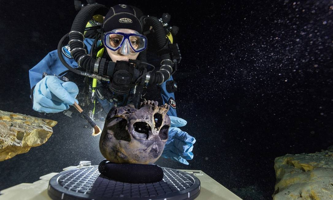 Na grande cúpula da caverna subaquática, a mergulhadora Susan Bird escova cuidadosamente o crânio encontrado para ser fotografado Foto: / Paul Nicklen