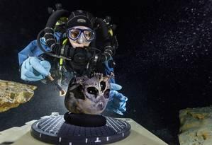 Na grande cúpula da caverna subaquática, a mergulhadora Susan Bird escova cuidadosamente o crânio encontrado para ser fotografado Foto: Paul Nicklen
