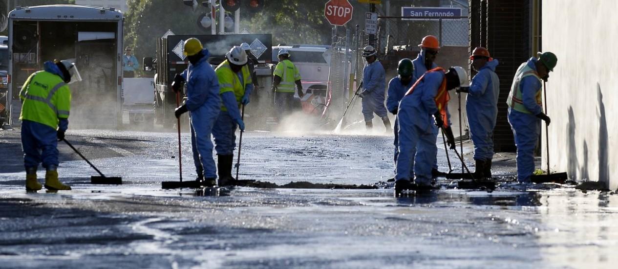 Funcionários limpam o petróleo que vazou de um oleoduto, em Los Angeles Foto: KEVORK DJANSEZIAN / AFP