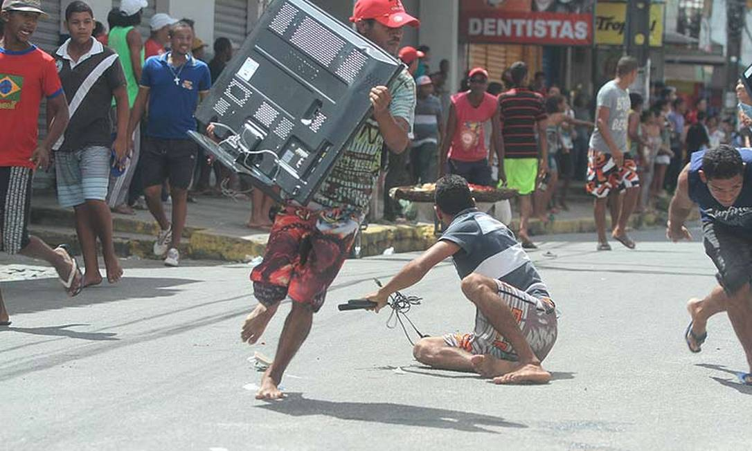 Um homem carrega um aparelho de TV durante saques a lojas no Grande Recife na quinta-feira Foto: Allan Torres/D.A Press