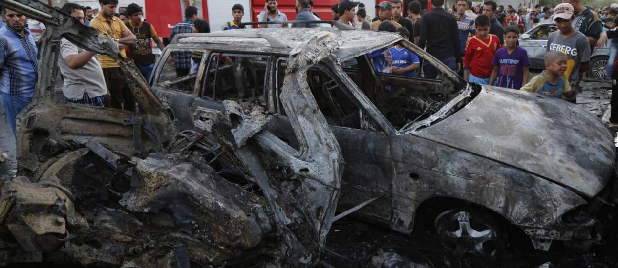 Moradores de Bagdá observam carro-bomba após detonação: Iraque foi o país com mais civis mortos por explosivos artesanais em 2013, segundo ONG Foto: Wissm al-Okili / REUTERS